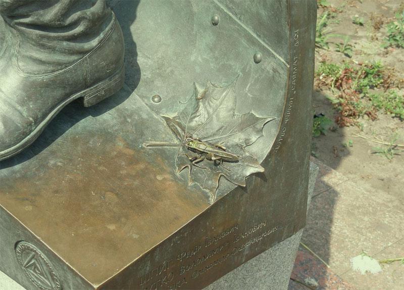 Фигурка кузнечика у ног Быкова